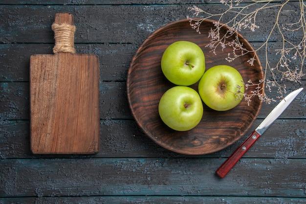 Draufsicht von weitem teller mit äpfeln holzteller mit appetitlichen äpfeln neben messerschneidebrett und ästen auf dunkler oberfläche