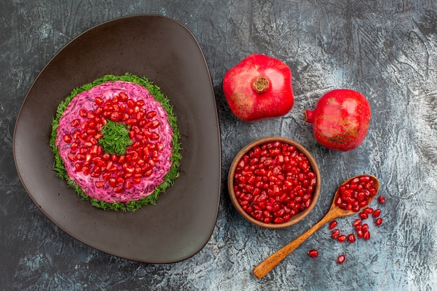 Draufsicht von weitem trägt ein appetitliches gericht mit kräutern granatapfelkernen des granatapfellöffels