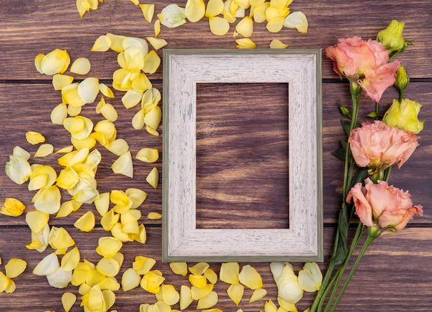 Draufsicht von wundervollen und frischen pfingstrosen mit gelben blütenblättern auf einer holzoberfläche
