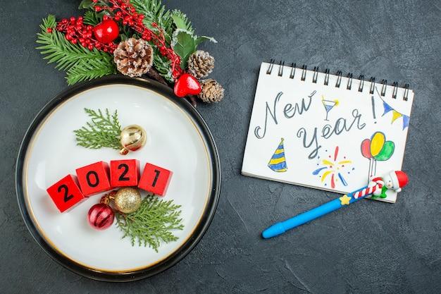 Draufsicht von zahlendekorationszubehör auf einer platte tannenzweige nadelbaumkegel und notizbuch mit neujahrsschrift und zeichnungen auf dunklem hintergrund