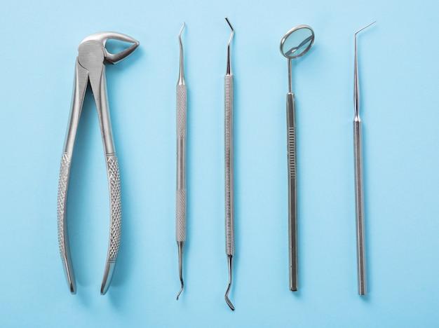 Draufsicht von zahnärztlichen werkzeugen auf blauem tisch in der zahnarztklinik: zahnspiegel, entdecker, pinzette.