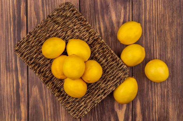 Draufsicht von zitronen der zitrusfrucht auf einem weidentablett mit den auf einer holzwand isolierten zitronen