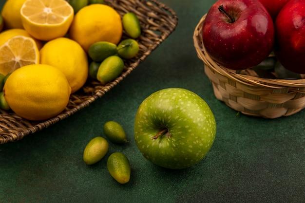 Draufsicht von zitronen der zitrusfrucht auf einem weidentablett mit kinkans mit grünem apfel auf einer grünen oberfläche