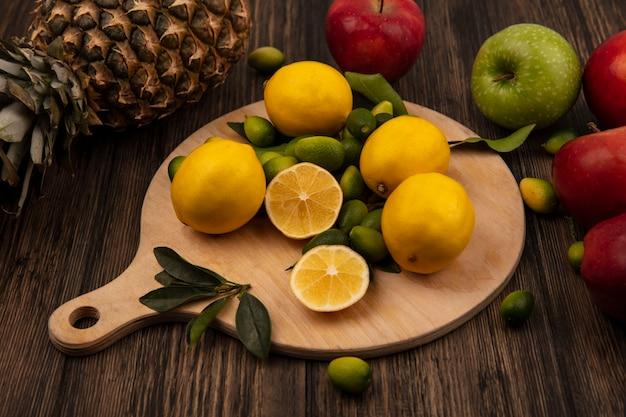 Draufsicht von zitronen mit kinkans lokalisiert auf einem hölzernen küchenbrett mit äpfeln und ananas lokalisiert auf einer holzwand