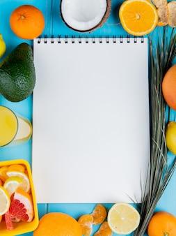 Draufsicht von zitrusfrüchten als mandarinen-avocado-kokosnuss-grapefruit-zitrone und zitronensaft mit notizblock in der mitte auf blauem hintergrund mit kopienraum