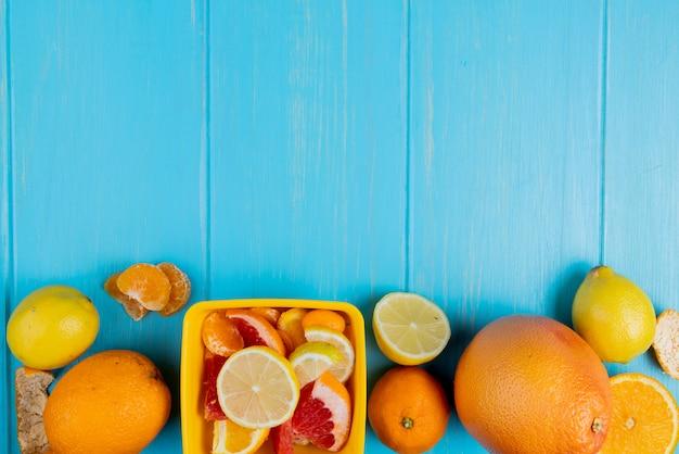 Draufsicht von zitrusfrüchten als mandarinen-zitronen-grapefruit auf blauem hintergrund mit kopienraum