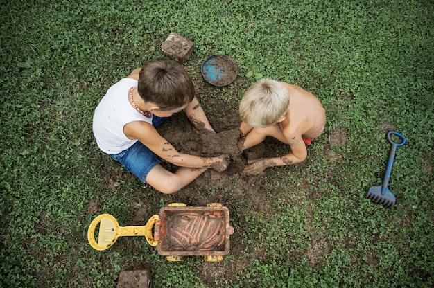 Draufsicht von zwei brüdern, die auf gras sitzen und mit schlamm spielen