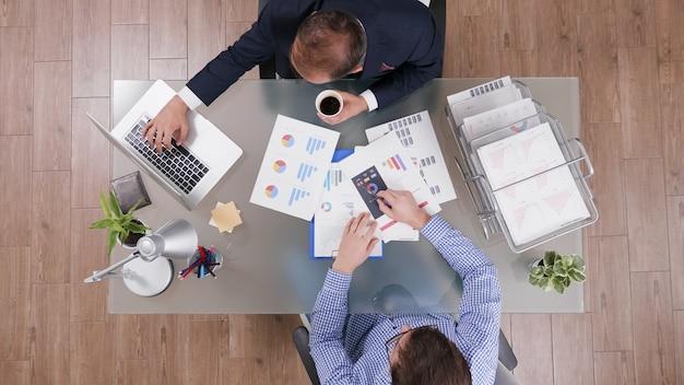 Draufsicht von zwei geschäftsleuten, die bei unternehmensinvestitionen arbeiten und geschäftsdokumente analysieren