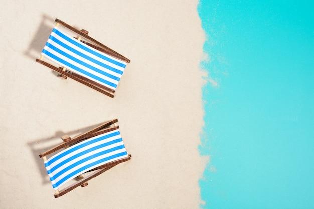 Draufsicht von zwei hölzernen liegestühlen in reihe am strand.