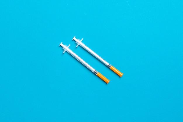 Draufsicht von zwei insulinspritzen bei buntem