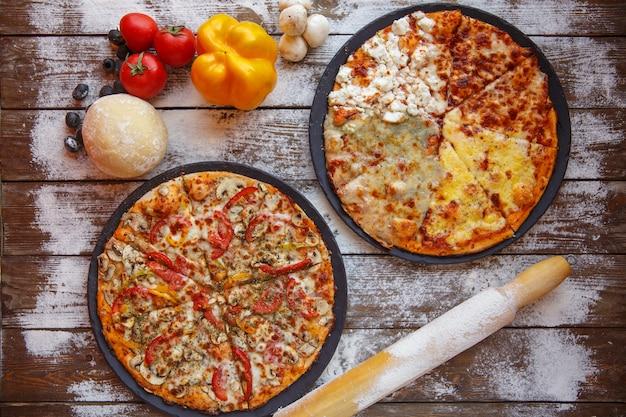 Draufsicht von zwei italienischen pizzen, die auf hölzernem hintergrund im mehl gedient werden, besprüht