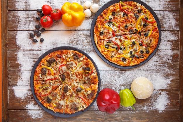 Draufsicht von zwei italienischen pizzen mit fleisch, grünem pfeffer, olive und pilz