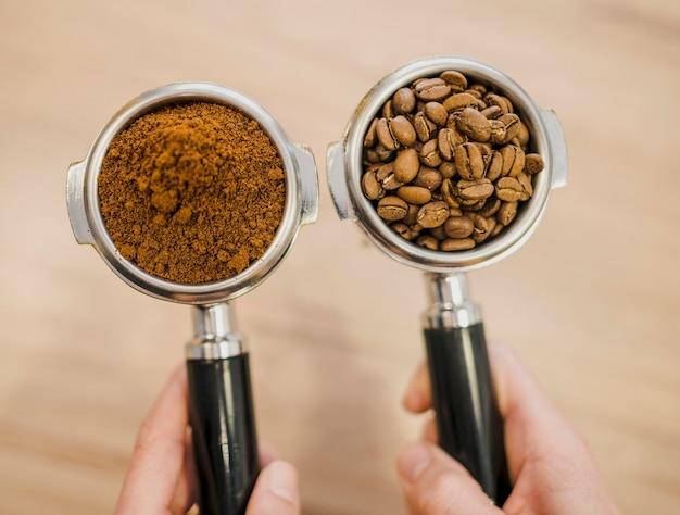 Draufsicht von zwei kaffeemaschinenbechern, die von barista gehalten werden