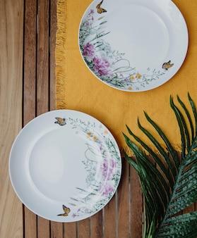 Draufsicht von zwei leeren platten des tisches mit blumenmuster auf einer gelben serviette auf holzwand