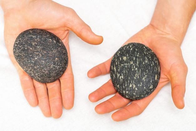 Draufsicht von zwei männlichen händen mit schwarzen heißen steinen, die auf einem weißen handtuch im schönheits-spa liegen