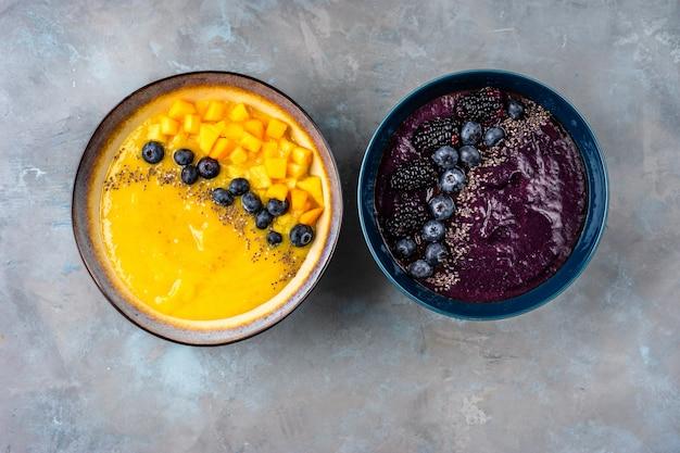 Draufsicht von zwei platten mit den gelben und violetten smoothies