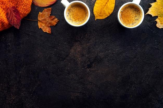 Draufsicht von zwei tasse kaffees um gelbe blätter
