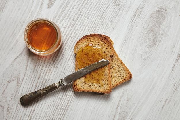 Draufsicht von zwei toast vom organischen rustikalen trockenen roggenbrot mit handwerklichem honig lokalisiert auf gealtertem gebürstetem weißem holztisch und weinlesemesser auf croutons