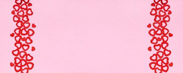 Draufsicht von zwei vertikalen streifen von kleinen herzförmigen konfetti auf rosa hintergrund, kopienraum. valentinstag banner.