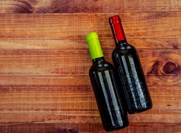 Draufsicht von zwei weinflaschen auf einer rustikalen hölzernen tabelle