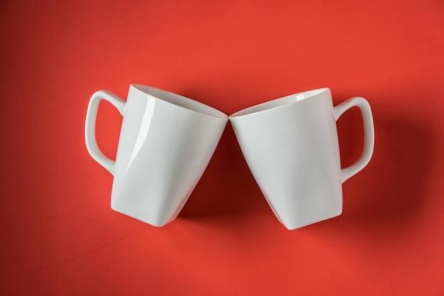 Draufsicht von zwei weißen keramischen kaffeetassen in einem roten
