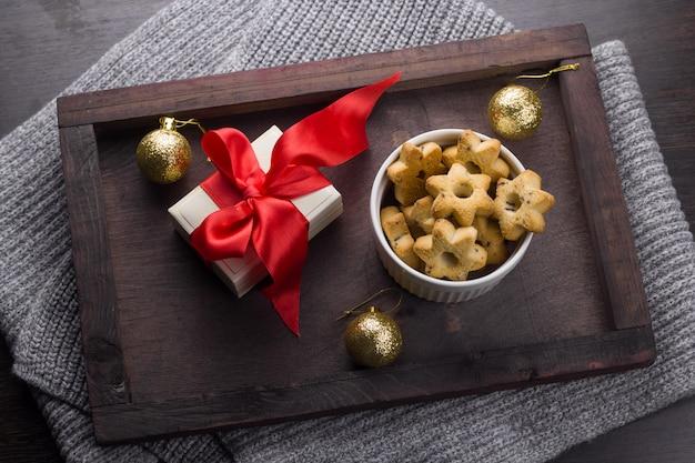 Draufsicht vorhanden mit rotem bogen, plätzchen in form der sterne und goldenen weihnachtsbällen