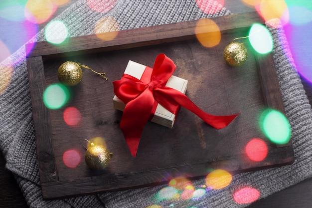 Draufsicht vorhanden mit rotem bogen und goldenen weihnachtsbällen mit glänzendem hellem bokeh