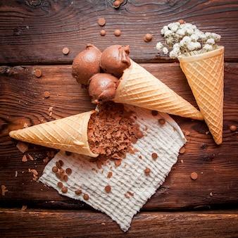 Draufsicht waffeltüten mit schokoladeneis und gypsophila und schokoladenstückchen in lappenservietten