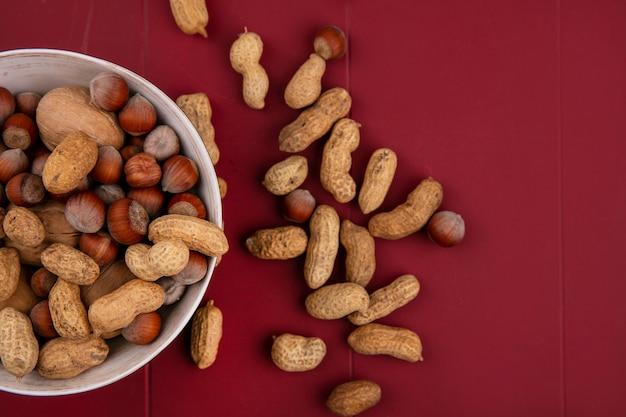 Draufsicht walnüsse mit haselnüssen und erdnüssen in einer schüssel auf einem roten tisch