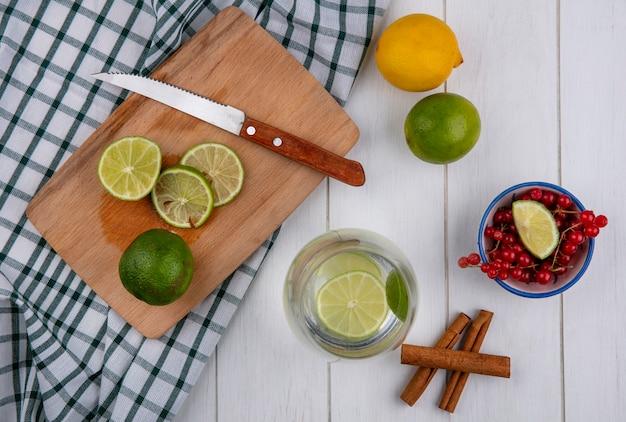 Draufsicht wasser in einem glas mit limette und zitrone auf einem brett mit einem messer und zimt auf einem weißen tisch
