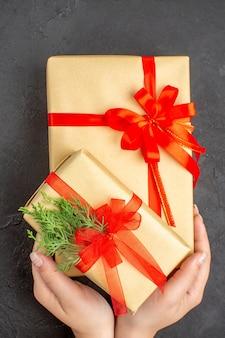 Draufsicht weibliche hände, die große und kleine weihnachtsgeschenke in braunem papier halten, die mit rotem band auf dunkler oberfläche gebunden sind