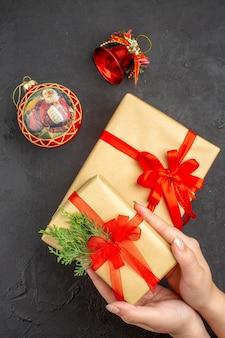 Draufsicht weibliche hände, die weihnachtsgeschenk in braunem papier halten, das mit rotem band-weihnachtsbaumspielzeug auf dunkler oberfläche gebunden ist