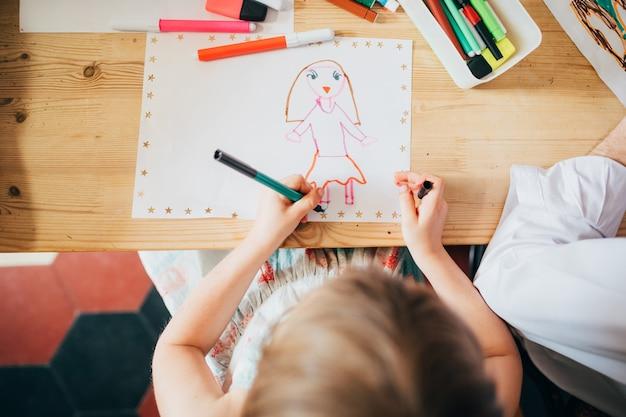 Draufsicht weibliche kinder sitzen tischzeichnung - phantasie, kreativität, aktivitätskonzept