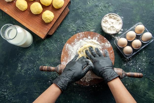Draufsicht weibliche köchin, die teig mit mehl auf dunkler oberfläche ausrollt