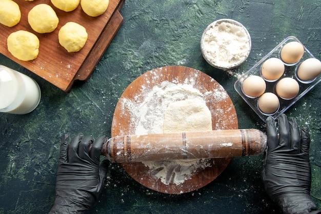 Draufsicht weibliche köchin, die teig mit mehl auf einer dunklen oberfläche ausrollt