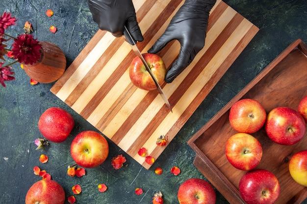 Draufsicht weiblicher koch, der äpfel auf der grauen oberfläche schneidet