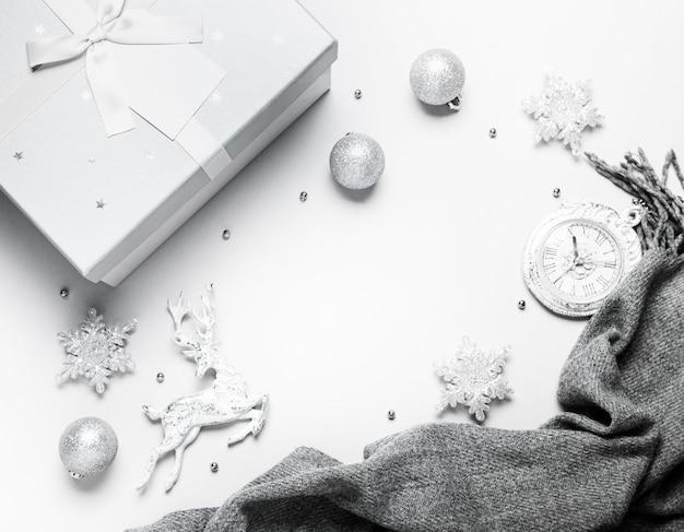 Draufsicht weihnachts- oder des neuen jahreszusammensetzung auf einem grauen und weißen hintergrund mit weißen und silbernen weihnachtsdekorationen, rotwild, schneeflocken, bällen und uhr
