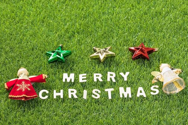 Draufsicht weihnachtsalphabet und -dekoration auf grünem gras