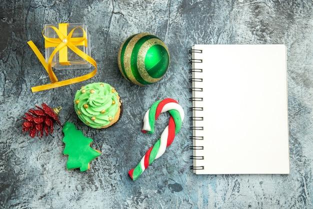 Draufsicht weihnachtsbaum cupcake weihnachtsbonbons weihnachtsbaum spielzeug notizblock auf grauer oberfläche