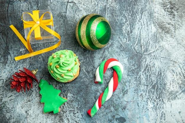 Draufsicht weihnachtsbaum cupcake weihnachtsbonbons weihnachtsbaumspielzeug auf grauer oberfläche freier platz neujahrsfoto