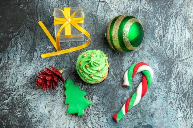 Draufsicht weihnachtsbaum cupcake weihnachtsbonbons weihnachtsbaumspielzeug auf grauer oberfläche