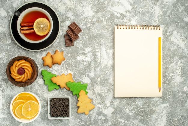 Draufsicht weihnachtsbaumplätzchen tasse tee schalen mit schokolade und zitronenscheiben notizbuchstift auf grauem tisch