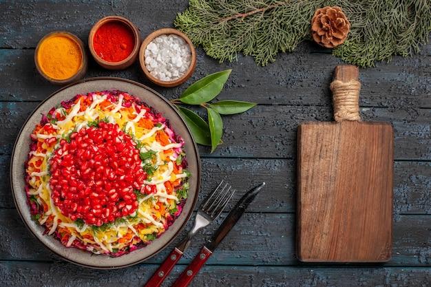 Draufsicht weihnachtsgericht mit granatapfel-karotten-kartoffeln neben dem holzbrett schüsseln mit verschiedenen gewürzen fichtenzweige mit zapfen auf dem tisch