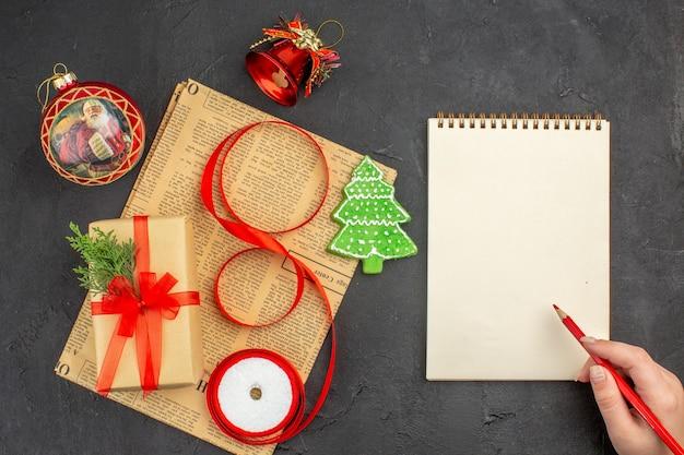 Draufsicht weihnachtsgeschenk in braunem papier zweig tannenband auf zeitung weihnachtsschmuck notizblock bleistift in weiblicher hand auf dunkler oberfläche