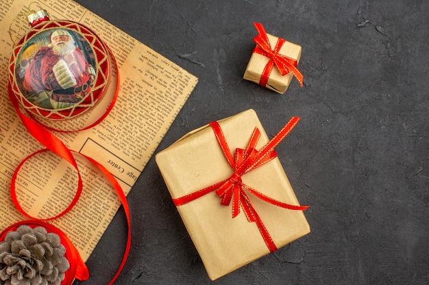 Draufsicht weihnachtsgeschenk in braunem papierband weihnachtsbaum spielzeug auf zeitung auf dunkler oberfläche
