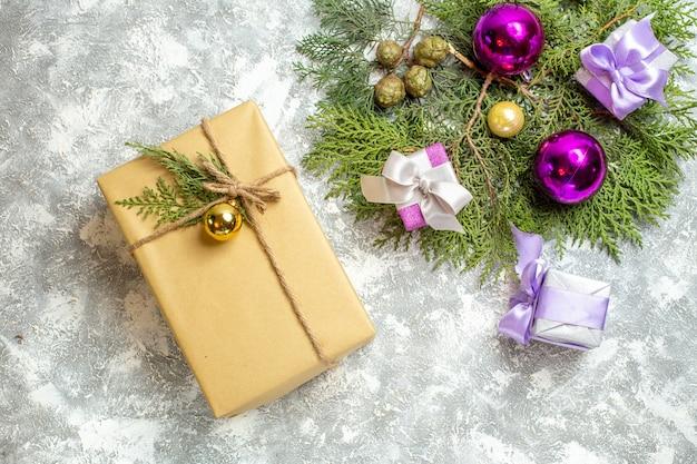 Draufsicht weihnachtsgeschenk kiefer zweige weihnachtsbaum spielzeug auf grauem hintergrund