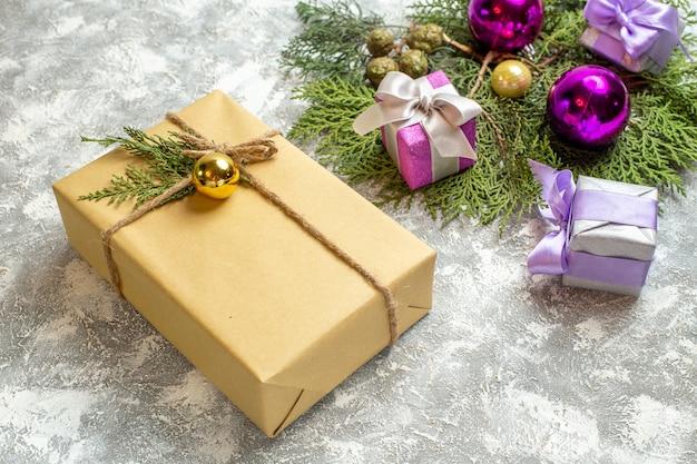 Draufsicht weihnachtsgeschenk kiefer zweige weihnachtsbaum spielzeug auf grauer oberfläche