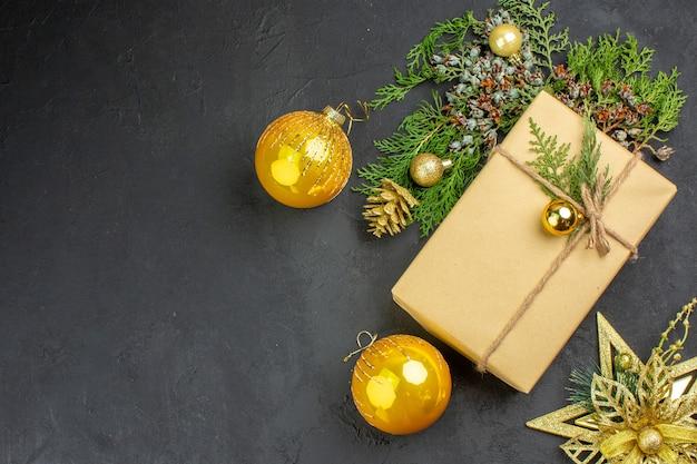Draufsicht weihnachtsgeschenk tannenbaum zweige weihnachtsbaum spielzeug auf beige oberfläche