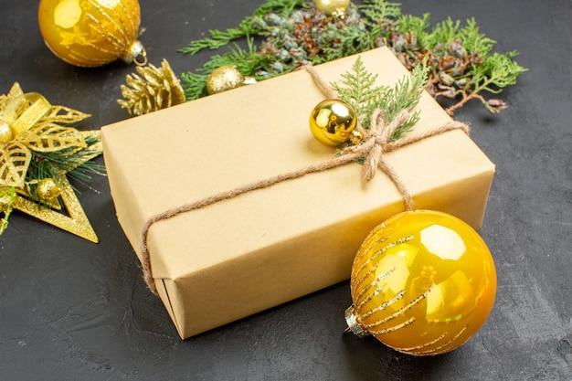 Draufsicht weihnachtsgeschenk tannenbaum zweige weihnachtsbaum spielzeug auf dunkler oberfläche