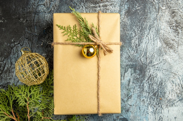 Draufsicht weihnachtsgeschenk tannenzweige weihnachtskugel auf grauer oberfläche